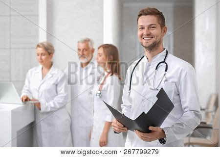 Medical Staff Of Professional, Private Hospital. Handsome Male Doctor Standing, Looking At Camera An