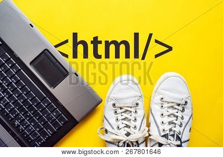 Man Legs In Shoes Standing Next To Laptop And Html Tag On Yellow Background