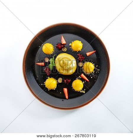 Fruit Dessert with Strawberries and Mango Sphere Isolated on White Background. Exquisite Serving Dish of Golden Ducky Cake with Apricots, Grapes and Berries on Elegant Restaurant Black Plate Top View
