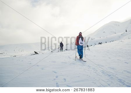 Ski Touring Couple Hiking Up A Summit In The Winter Mountains
