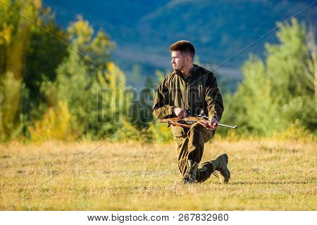Man charging hunting rifle. Hunting as male hobby and leisure. Hunting shooting trophy. Hunter khaki clothes ready to hunt hold gun mountains background. Hunter with rifle looking for animal poster