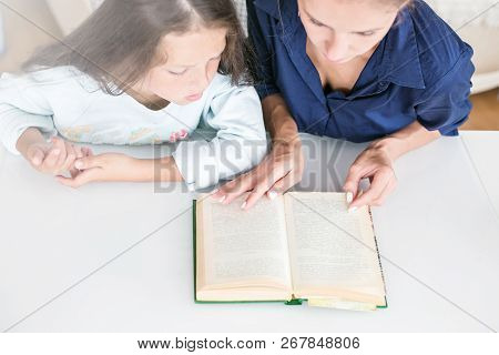 Happy Family Mother And Daughter Read A Book In The Evening At Home. The Concept Of Family Comfort A
