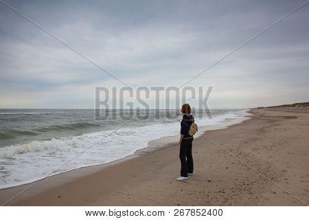 Hvide Sande, Denmark - August 13,2018: Lonely Woman On The Beach. Hvide Sande In Denmark Has 40 Km S
