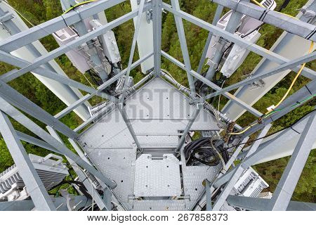 Telecommunication tower with microwave, radio antennas, remote radio units, power and optic cables poster