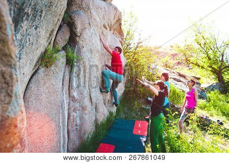A Rock Climber Climbs A Rock And His Partner Insures. Athletes Are Bouldering Outdoors. Group Of Fri