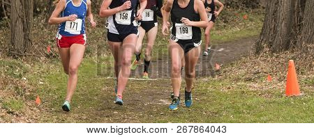 High School Girls Running A Cross Country Race On A Dirt Path With Arrows And Cones Marking The Path