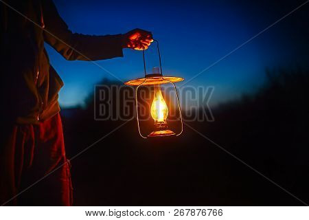 Hand Holds A Large Old Lamp In The Dark. Man Holding The Vintage Lamp With A Candle Outside. Copy Sp