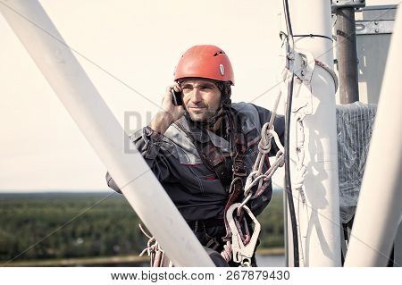Tower Technician Talking On A Cell Phone On A Telecommunications Tower. The Concept Of Checking Cell