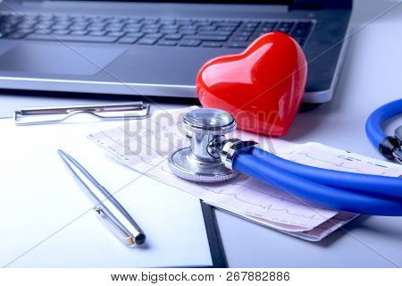 Workplace Of Doctor With Laptop, Stethoscope, Red Heart And Rx Prescription On White Table. Top View