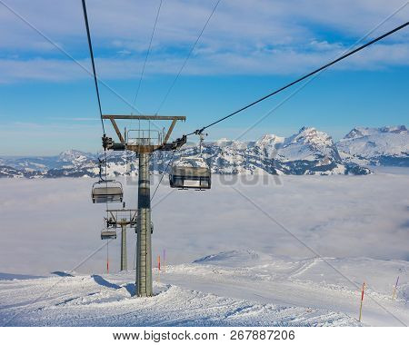 An Overhead Cable Car, Summits Of The Alps Rising From Sea Of Fog - A Wintertime View From The Frona
