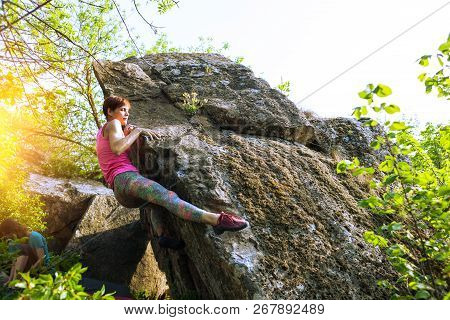Climber Is Bouldering In Nature. Girl Climbs On A Big Stone. Woman Doing Sports Outdoors. Athlete Is