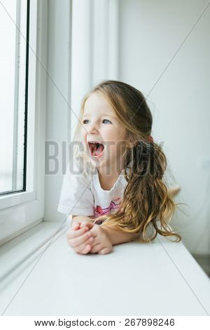 Beautiful Little Girl Smiling And Watching Out The Window. A Child Looks Out The Window. Young Girl