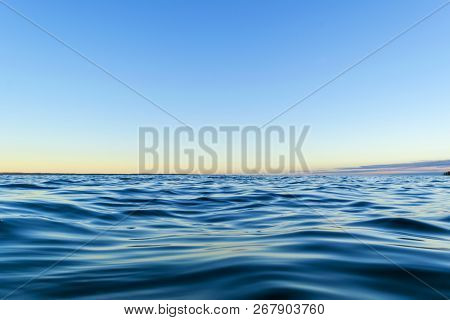 Water Surface. View Of A Sunset Sky Background. Dramatic Gold Sunset Sky With Evening Sky Clouds Ove