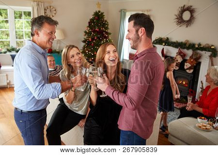 Multi-Generation Family And Friends Making A Toast With Champagne At Christmas House Party