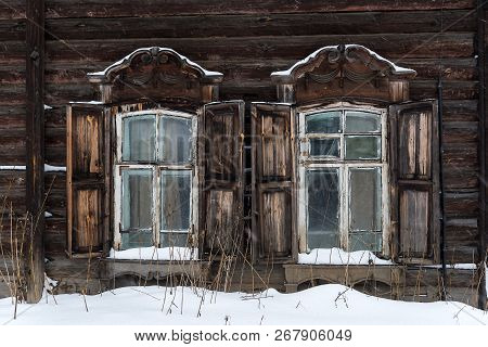 The Windows Of An Old Wooden Residential House On A Winter Day