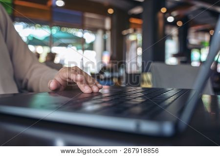Closeup Image Of Hands Using And Touching On Laptop Touchpad On Wooden Table
