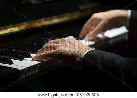 Professional Musician Pianist Hands On Piano Keys Of A Classic Piano In The Dark.