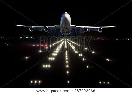 A Passenger Plane Takes Off From The Night Airport Runway. Airplane Front View.