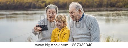 Senior couple with great-grandson take a selfie in the autumn park. Great-grandmother, great-grandfather and great-grandson BANNER, LONG FORMAT poster