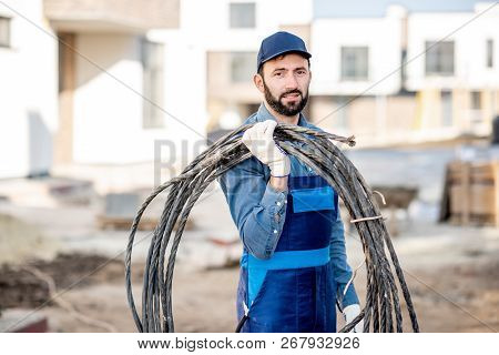 Portrait Of A Handsome Electrician In Uniform With Power Cable For The Network On The Construction S