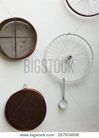 Sieves, bicycle wheels and  a ladle hung on a white wall of a traditional Lefka Cyprus house for decoration purposes poster