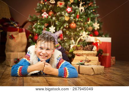 Christmas Child Under Xmas Tree, Happy Boy Kid Lying On Wood Floor Front Of New Year Presents Gifts