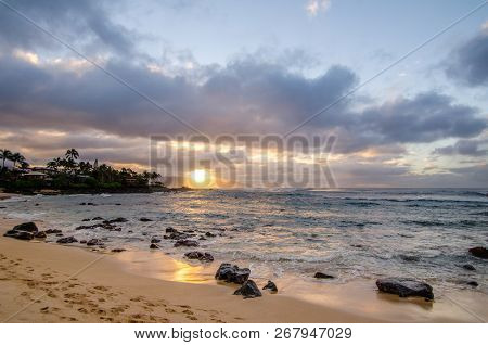 Waves Rolling In Over Small Coral Rocks On The Shore At Sunset On The North Shore Of Oahu, Hawaii