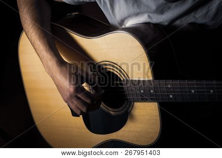 The Young Man Playing An Acoustic Guitar In The Studio