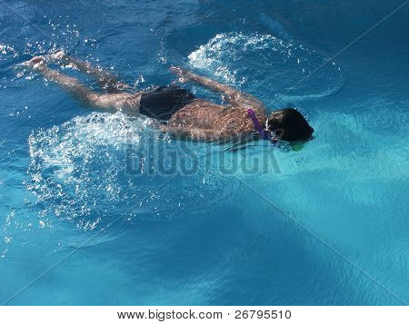 A young boy diving under water surface