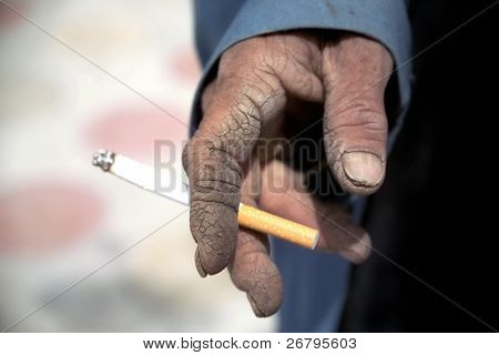 close up shot of hand holding cigarette