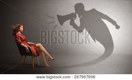 Dark shadow yelling with loudspeaker to elegant young lady
