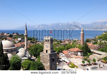 close up shot of a clock tower and minaret in Antalya poster