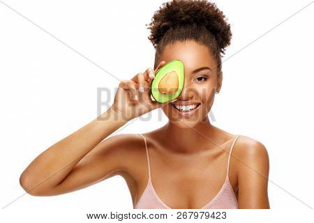 Pretty Young Woman Holding Half An Avocado In Front Of Her Face. Photo Of Smiling African Woman Isol