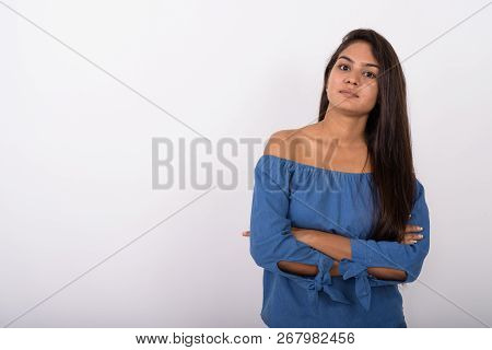 Studio Shot Of Young Indian Woman With Arms Crossed Against Whit