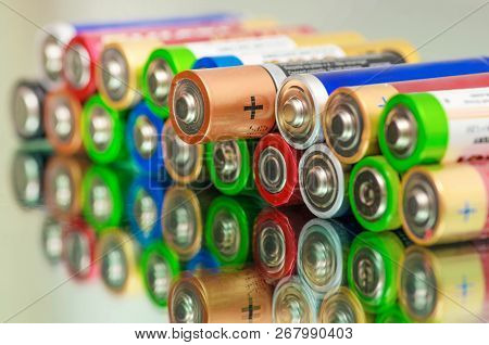 Closeup of pile of used alkaline batteries. Rows of selection of AA batteries energy abstract battery background. Alkaline battery aa size. Storage batteries in rows. Dead battery. Disposal battery. Waste battery. Battery energy. Battery recycling.