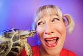 Funny woman with tortoise on vivid color background poster