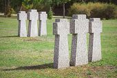 cemetery with identical old memorial headstones placed in rows poster