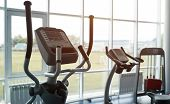 Elliptical trainer in a fitness gym club with row of trainers for fitness cardio training on the background. Modern gym interior with equipment. poster