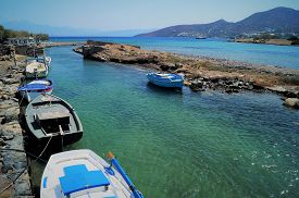 Fishing Boats In Elounda. Small Traditional Fishing Boats Line A Canal In The Picturesque Town Of El