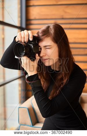 Young Photographer With Camera Taking Photo On Professional Photo Shoot With Day Light Near Window