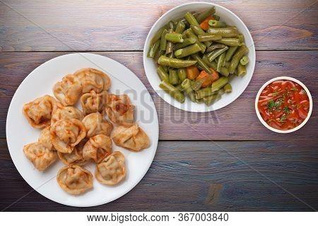 Dumplings On A White Plate On Purple Wooden Background. Dumplings In Tomato Sauce With Salad. Dumpli