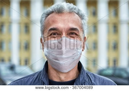 Smiling White Caucasian Man In A Disposable Protective Surgical Mask In A Period Of Coronavirus Covi
