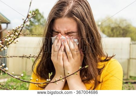 Allergic teen girl near a tree sneezes