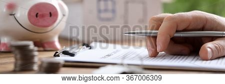 Man Fills In Lease Document At Home, On Piggy Bank. Composition And Value Property, Taking Into Acco
