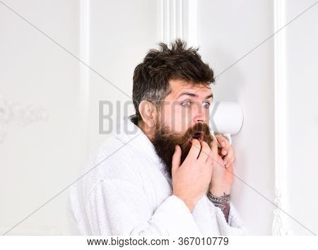 Man With Beard And Mustache Eavesdrops Using Cup Near Wall. Privacy Concept. Hipster In Bathrobe On