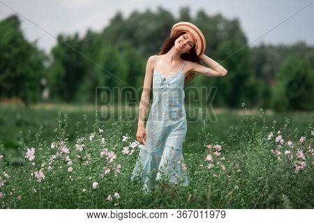 girl in a blue sundress on a flower field