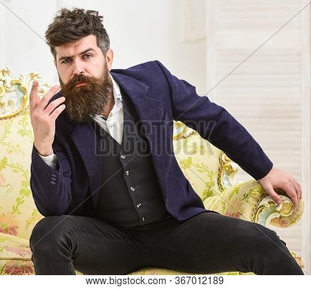 Macho Attractive And Elegant On Serious, Thoughtful Face Sitting On Old Fashioned Luxury Sofa. Man W