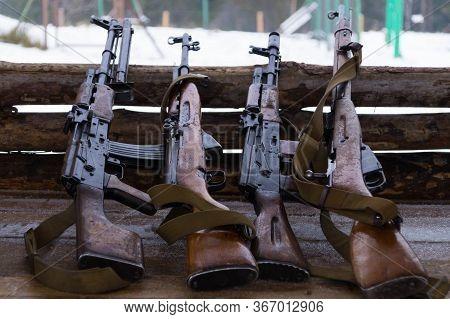 Four Guns Lie, Leaning Their Trunks On Wooden Barricades