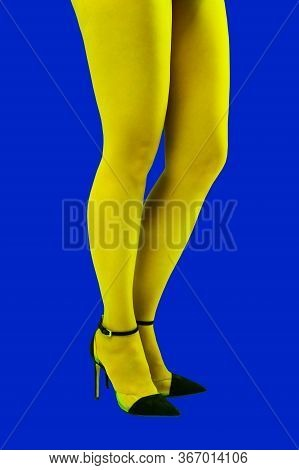 Close-up Picture Of Womans Beautiful Yellow Legs In High Heels Shoes On Acid Blue Color Background.