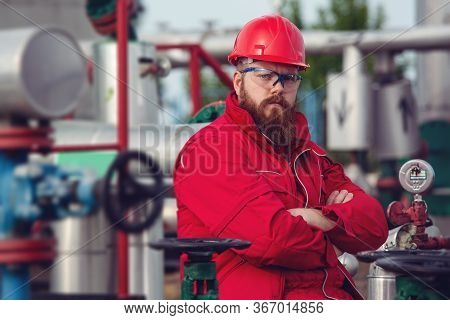 Portrait Of An Engineer In Front Of A Petrochemical Industry.